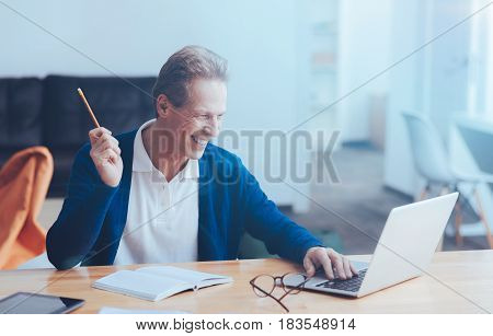 Little success. Cheerful adult smiling man sitting at the table and using laptop while workign as a freelancer