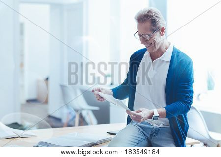 Involved in work. Positive handsome experienced man holding papers and sitting in the office while working on the project