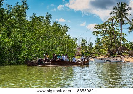 Ambatozavavy Nosy Be Madagascar - December 19 2015: Locals on the traditional wood pirogue with outrigger on the shore of the fishing village on the Nosy Be island Madagascar.