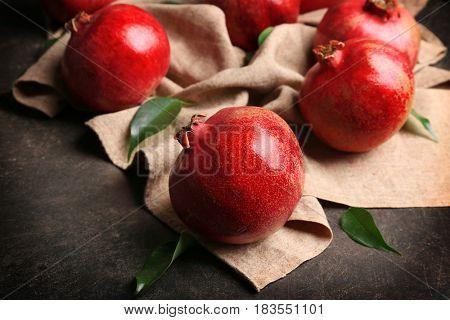 Whole pomegranates with napkin on gray background
