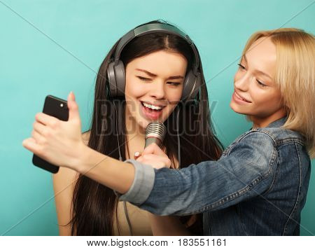 lifestyle, emotion  and people concept: Happy girls  with microphone