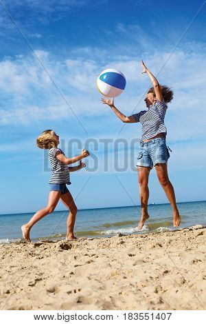 Happy parent and child play a ball at coast on a sunny summer day. Beach sports