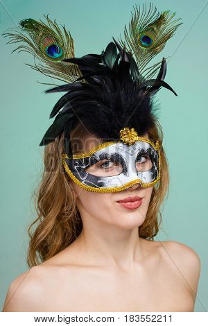Carnival dancer woman wearing a mask posing on green background