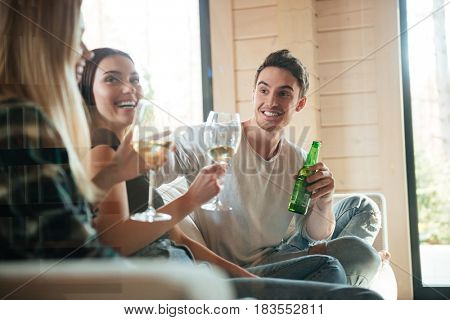 Group of cheerful young friends drinking wine and beer on sofa at home