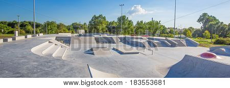 Empty concrete skatepark. Beautiful weather and blue sky.