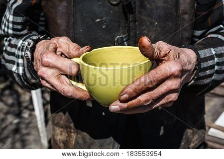 homeless old man holding cup of tea
