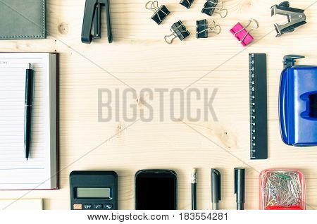 Office desk table with book planner pen calculator wallet pencil ruler stapler paper clips clamps sharpener round copy space field. Top view of office desk flat lay. Business background.