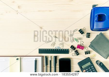 Office desk table with book planner pen calculator wallet pencil ruler stapler paper clips clamps sharpener on left. Top view with copy space flat lay. Business background.
