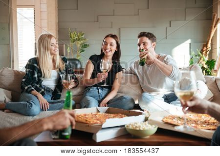 Group of cheerful young friends with pizza, wine and beer talking and having fun on sofa at home