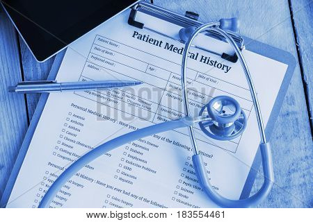 Patient medical history on a clipboard with stethoscope and a blue ballpoint pen, putting on a physician's table. Blank form waiting to be filled and reviewed / examined by nurse / clinical assistant.