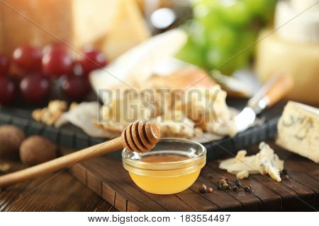 Dipper with honey in bowl and different types of cheese on background