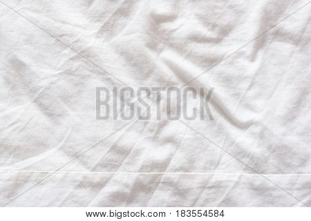 Top view of wrinkles on an untidy white bed sheet in a bedroom after a long night sleep and waking up in the morning. Abstract texture background.