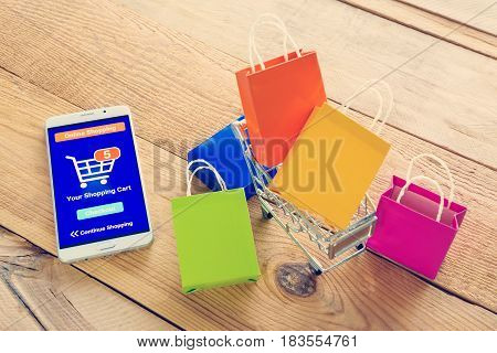 White smartphone runs an online shopping app put near colorful paper shopping bags and a shopping cart. Consumers can buy everything from online stores using a smart device connects to the internet.