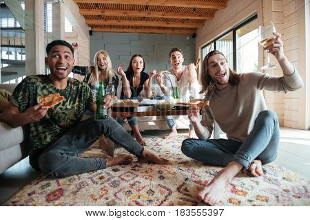 Screaming Happy Five friends are sitting in house and eating pizza while looking away