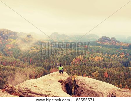 Photographer Takes Picture Of Spring Nature From Sharp Rocks. Hiker In Green Jacket Stay With Camera