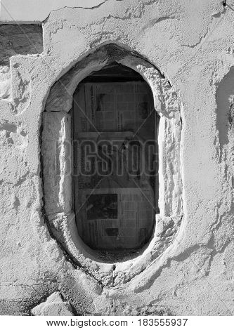 oval window in an old distressed white wall blocked with newspaper