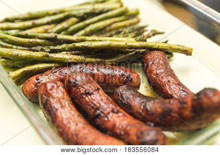 Grilled brats or sausages and asparagus in glass dish.
