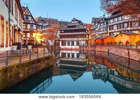 Traditional Alsatian half-timbered houses in Petite France with mirror reflections during morning blue hour, Strasbourg, Alsace, France