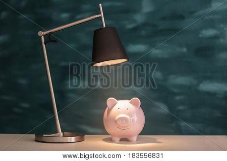 Cute pink piggy bank on illuminated surface under lamp