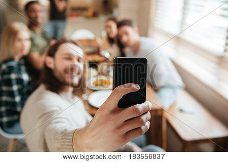 Attractive young man taking a selfie photo with friends in the kitchen while having lunch together at home, focus on mobile phone