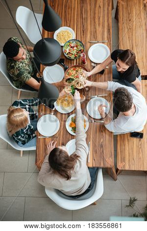 Top view of five people cheering with wine while sitting at the rustic dining table