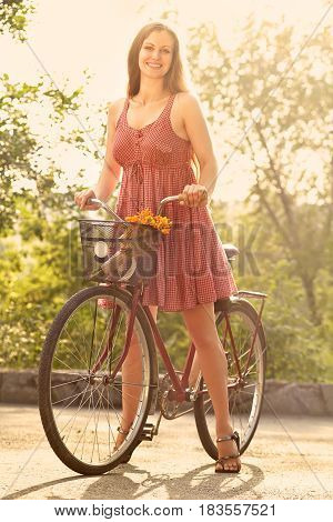 young woman in a dress with a bike in a summer park. Active people. Outdoors