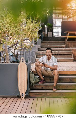 Portrait of a young Asian man smiling and sending text messages on his cellphone, while sitting alone on some stairs next to his long board outside