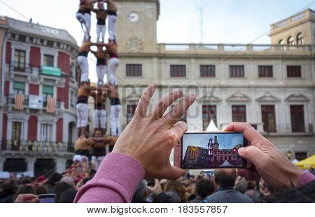 Hand held smartphone taking a picture of Castells Performance. a castell is a human tower built traditionally in festivals within Catalonia. Is also UNESCO Intangible Cultural Heritage of Humanity