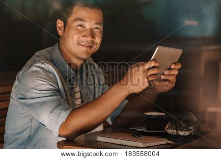 Close up portrait of happy young Asian man using a digital tablet while sitting alone in a cafe drinking a cup of coffee