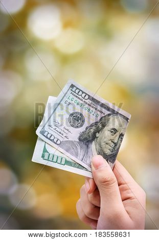 Money in hand isolated on orange background bokeh