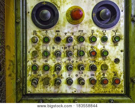 old analog mechanical press control panel under layer of oil and dirt