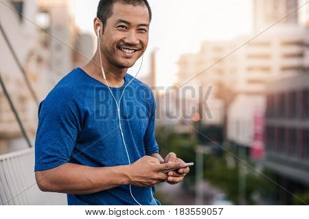 Portrait of a smiling young Asian man in sportswear standing outside listening to music on an mp3 player while out for a city run