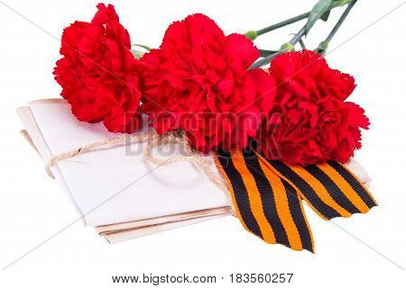 A stack of letters tied with a rope along with red carnations and ribbon to the day of victory on a white background