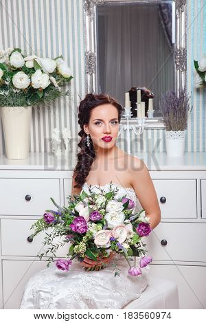 Wedding. Bride in beautiful dress sitting on sofa indoors in white studio interior like at home. Trendy wedding style shot in full length.Young attractive caucasian brunette model like a bride