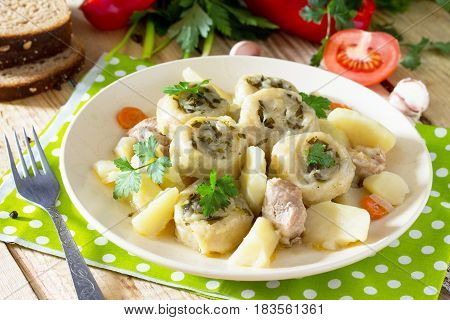 Potatoes Stewed With Meat And Rolls Of Dough With Garlic And Greens On A Wooden Table, Served With F