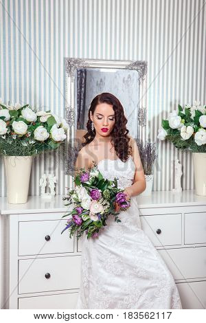 Young attractive bride with flowers indoors . Bride's morning. Fine art wedding. Happy Bride waiting groom.