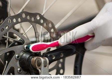 Closeup hand wearing white glove holding toothbrush rubbing on metal bicycle chain, mechanical repair concept.