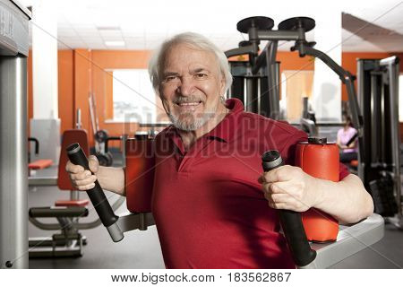 Elderly man using rotary torso trainer in gym