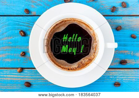 Hello May text on a cup of coffee at blue wooden background. Top view.