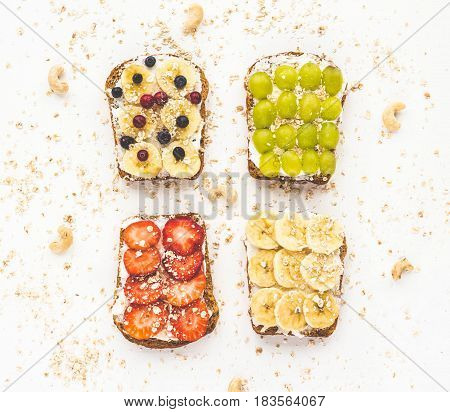 Healthy fruit breakfast. Fruit toasts with banana cream cheese grapes berry strawberry cereals and nuts on white background. Top view flat lay.