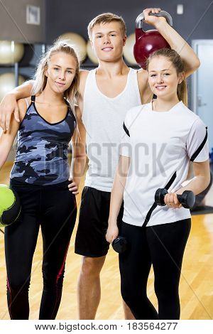 Portrait of confident young man with female workout team friends standing in fitness gym