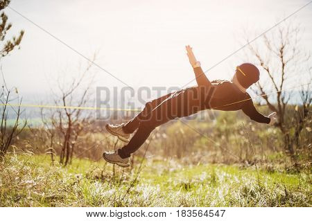 A man with a beard and in sunglasses lying balancing a stretching rope or an open-air canopy under the open sky, a slaskening nature in the spring, a balance, a learning concept