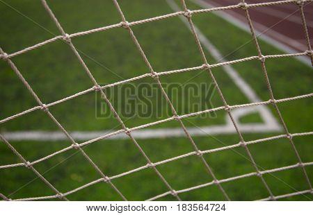 Football field. Point corner kick. Green synthetic grass. Net grid closeup
