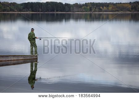 fisherman on the shore of a lake, a river with a fishing rod, is fishing