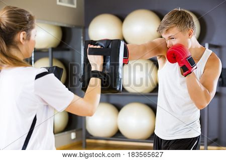 Young male boxer punching bag held by instructor in health club. Two young and focused people trains boxing in pairs. Sparring as workout at the fitness gym.