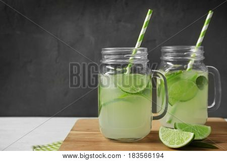 Glass jars of bracing cocktail with lime slices on wooden board against dark background