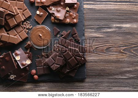 Slate plate with melted chocolate and chopped bars on wooden background