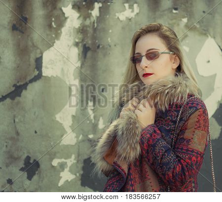 Young woman near cracked wall. Toned image
