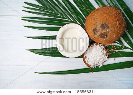 Delicious coconuts with flakes and milk on palm leaf on white wooden table
