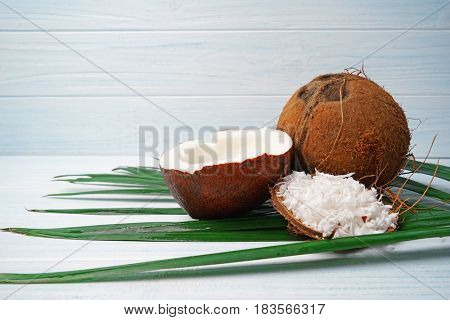 Delicious coconuts with flakes and milk on palm leaf on white wooden background